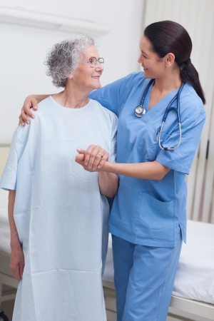 Nurse assisting an elderly patient in hospital ward photo