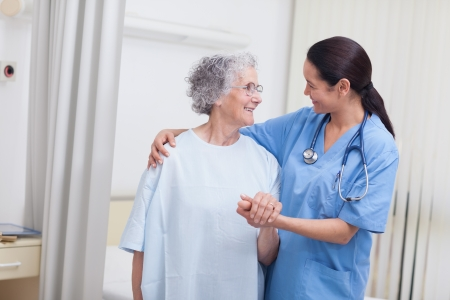 Nurse and a patient standing in hospital ward photo