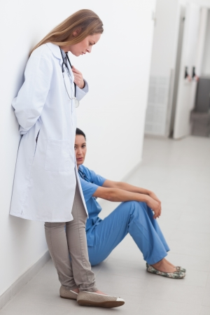 Doctor standing next to a nurse sitting on the floor in hospital ward photo