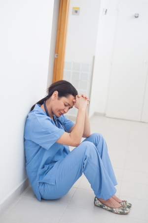 Sad nurse sitting on the floor in hospital ward photo