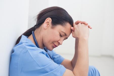 leaned: Upset nurse sitting on the floor in hospital ward