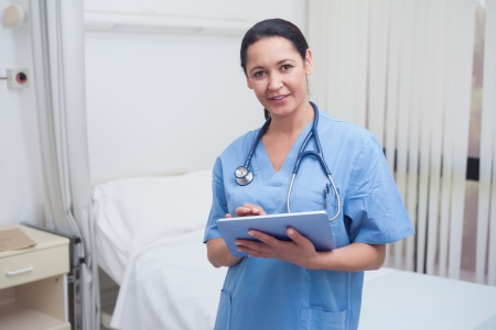 Nurse using a tablet pc in hospital ward photo