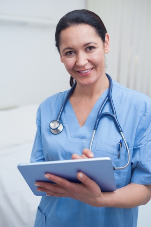 black nurse: Nurse looking at camera while holding an ebook in hospital ward Stock Photo