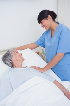 Nurse touching the shoulder of a patient in hospital ward photo