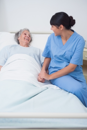 Nurse sitting on the medical bed next to a patient in hospital ward photo