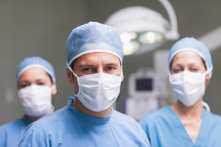 medical assistant: Medical team looking at camera in operating theater