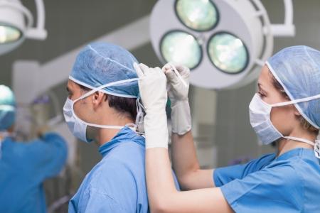 enfermera con cofia: Enfermera atar la m�scara del m�dico en la sala del hospital Foto de archivo