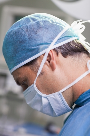 serious doctor: Serious doctor performing surgery in close-up
