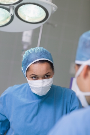 Serious nurse looking at a doctor in operating theater photo