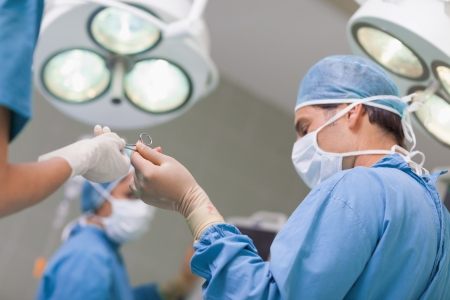Doctor receiving a surgical scissor from a nurse in operating theater photo