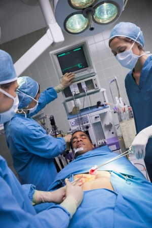 Serious doctors operating a patient in operating theater photo