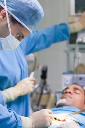 Doctor operating in operating theater photo