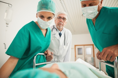 hospital corridor: Doctors looking at a patient while leaning on a bed in hospital corridor Stock Photo