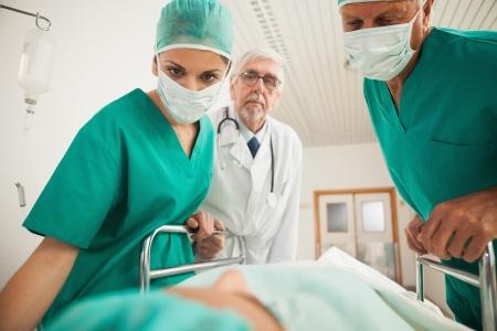 empujando: Los m�dicos mirando a un paciente mientras se inclina sobre una cama en pasillo del hospital