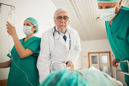 Doctor and surgeon looking at a patient in hospital hallway photo