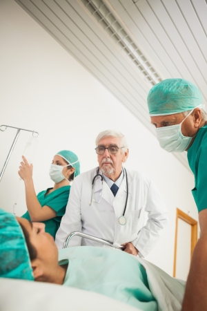 Doctor and surgeon looking at a female patient in hospital ward photo