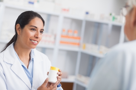 medicaments: Pharmacist holding a drug box while looking at a patient in hospital