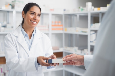 pharmacist: Smiling pharmacist giving a box to a doctor in hospital Stock Photo