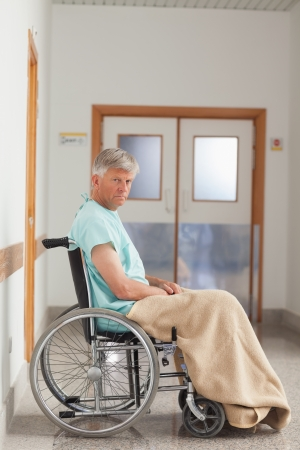 Patient sitting in a wheelchair with a blanket in hospital  photo