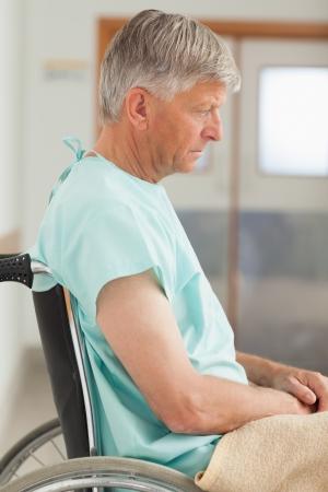 paraplegico: Hombre triste que se sienta en una silla de ruedas en el hospital