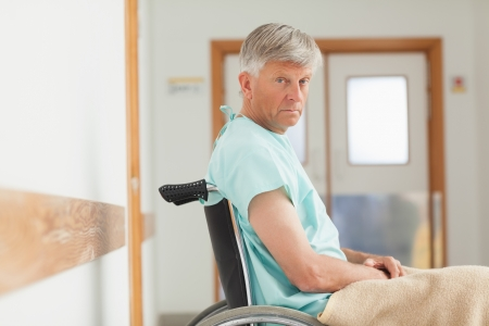 Man sitting in a wheelchair while looking at camera in hospital ward photo