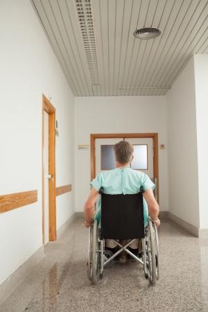 Male patient sitting in a wheelchair in the corridor in hospital  photo