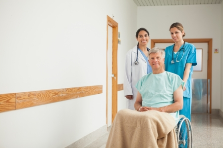 Patient in a wheelchair next to nurses in hospital  photo