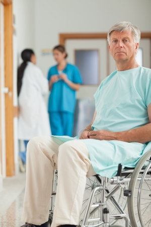 Patient in a wheelchair looking at camera in hospital corridor photo