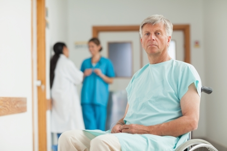 Male patient in a wheelchair looking at camera in hospital corridor photo