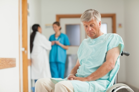 Patient in a wheelchair looking down in hospital ward Stock Photo - 16204555