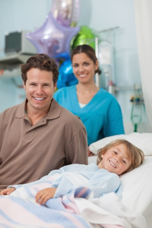 Child lying on a medical bed next to his father in hospital ward Stock Photo - 16207438