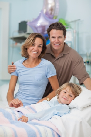 recovery bed: Bambino che giace su un letto medico accanto ai suoi genitori in reparto ospedaliero