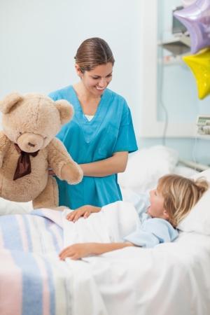 Krankenschwester h�lt einen Teddyb�ren in Krankenstation Lizenzfreie Bilder