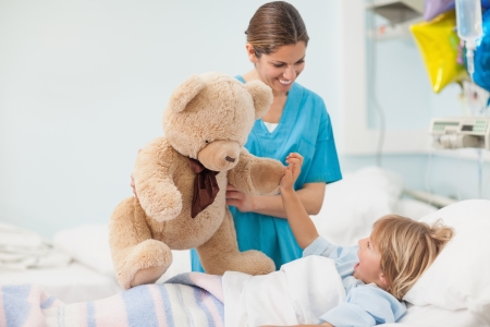 Nurse showing a teddy bear to a child in hospital ward photo
