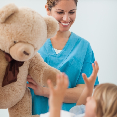 Smiling nurse holding a teddy bear in hospital ward Stock Photo - 16202421