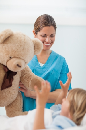 Smiling nurse showing a teddy bear to a child in hospital ward Stock Photo - 16204543