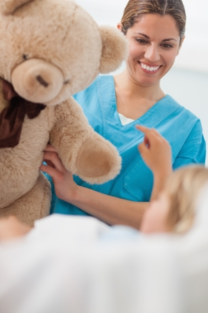 Happy nurse holding a teddy bear in hospital ward Stock Photo - 16204042
