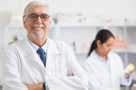 pharmaceutical: Pharmacist looking at camera with arms crossed in hospital