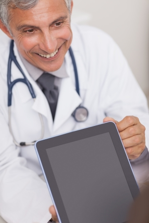 Doctor holding a tablet computer while smiling in medical office Stock Photo - 16203786
