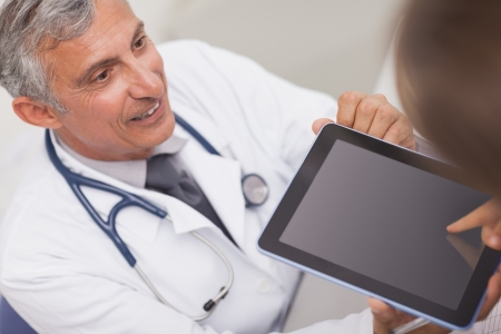Doctor holding a tablet computer while looking at a patient in medical office Stock Photo - 16204564