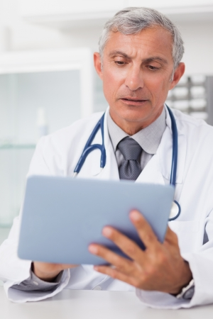 Doctor using a tablet computer in a medical office Stock Photo - 16202203