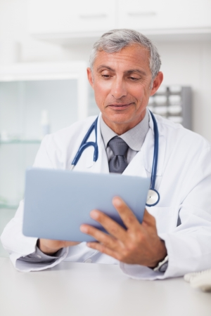 Smiling doctor using a tablet computer in hospital ward Stock Photo - 16203293