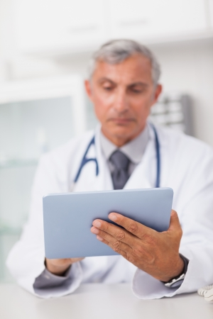 doctor tablet: Doctor holding a tablet computer while using it in a medical office Stock Photo