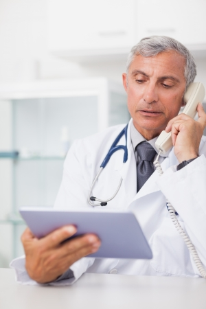 Doctor holding a tablet computer while calling in hospital ward Stock Photo - 16202800
