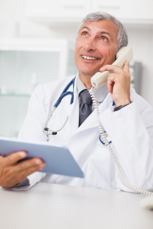 Doctor calling while holding a tablet computer in medical office Stock Photo - 16202784