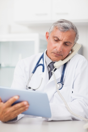 Doctor using a tablet computer while calling in medical office photo