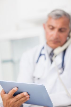 Focus on a doctor holding a tablet computer in hospital ward Stock Photo - 16202266