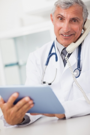 Smiling doctor holding a tablet computer and calling in medical office Stock Photo - 16203333