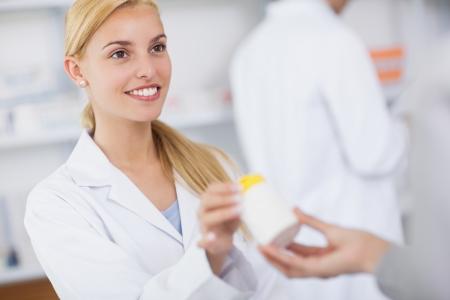 pharmaceutic: Blonde pharmacist giving a drug box in a hospital