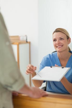 tied hair: Infermiera che chiede la firma di un paziente ad un ricevimento ospedale Archivio Fotografico